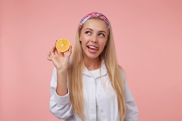 オレンジを手にポーズをとって、舌を抜いて脇を見て、カジュアルな服を着て美しい若いブロンドの女性