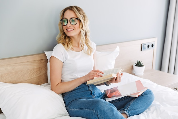 本を読んで、自宅のベッドでリラックスした美しい若いブロンドの女性