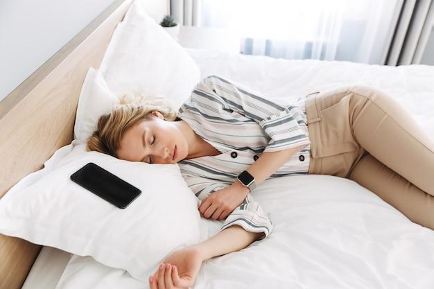 空白の画面の携帯電話で寝て、自宅のベッドでリラックスした美しい若いブロンドの女性