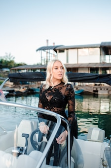 Beautiful young blonde woman, riding a boat on the water.