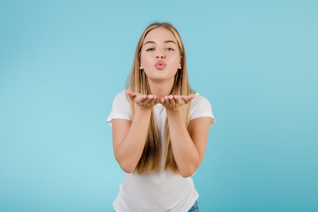 Beautiful young blonde woman sending smooch kiss isolated over blue
