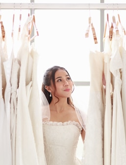 Красивая молодая блондинка стоя, выбирая свадебное платье. улыбающаяся азиатская дама, держащая свадебное платье невесты в примерочной в магазине. концепция прекрасной любви счастливый лучший день.