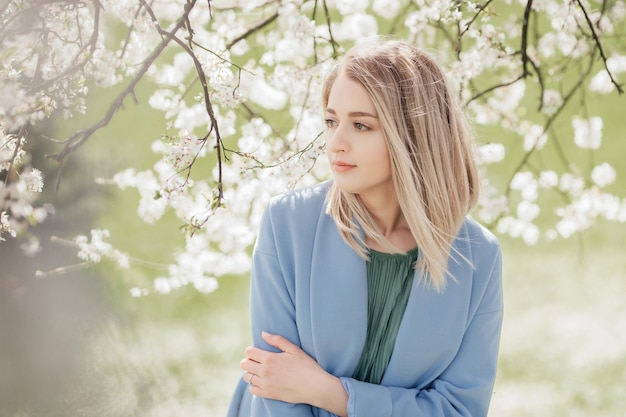 A beautiful young blonde woman standing near an apple tree in a green dress and a blue coat