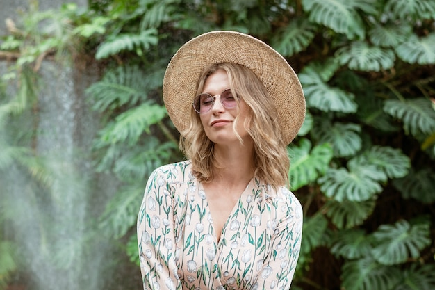 Beautiful young blonde woman in a straw hat and glasses posing in the park by greenery