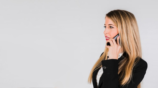 Beautiful young blonde woman talking on mobile phone against grey background