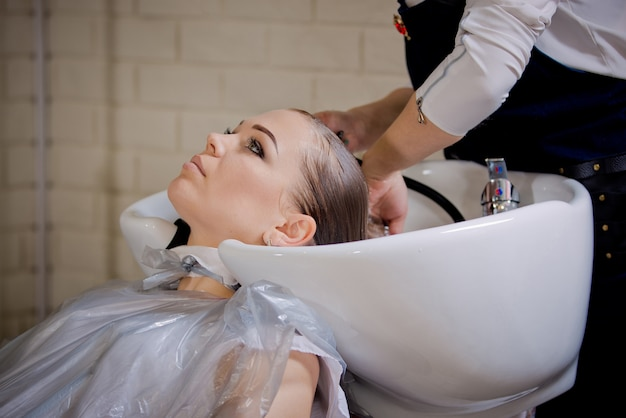 Beautiful young blonde woman washes her hair after dyeing.