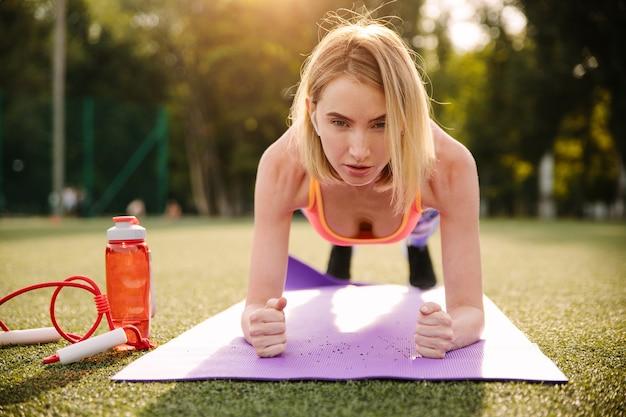陸上競技場で板運動を行うスポーツウェアを着ている美しい若いブロンドの女性