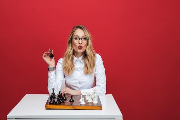 テーブルに座って、赤い背景で隔離のチェスを再生する白いシャツを着て美しい若いブロンドの女性