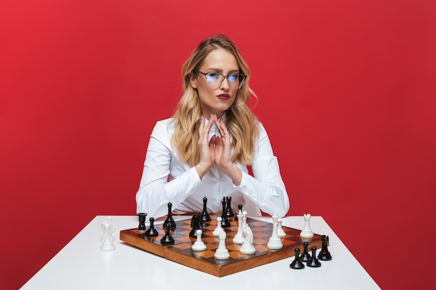 Beautiful young blonde woman wearing white shirt sitting at the table, playing chess isolated over red background