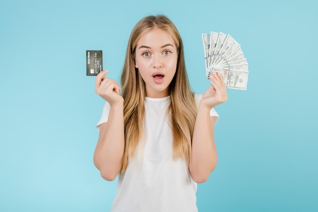 Beautiful young blonde woman with dollar money and credit card isolated over blue
