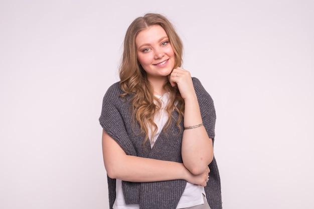 コピースペースと白い背景の上の灰色の特大のセーターと美しい若いブロンドの女性