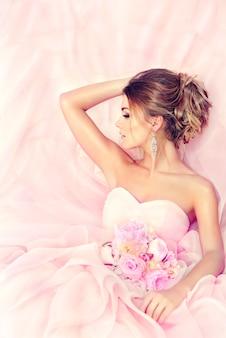 豪華な、バラのウェディングドレスに身を包んだ美しい若い花嫁は、手に花束を持っています