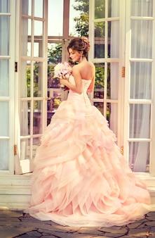 Красивая молодая невеста, одетая в традиционное европейское свадебное платье, держит букет в руке.