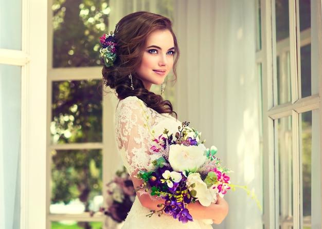 Красивая молодая невеста, одетая в свадебное платье, держит букет в руках.