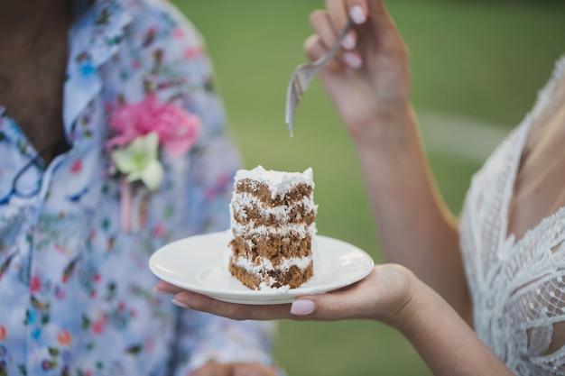 Beautiful young bride feeding wedding cake to groom outdoors