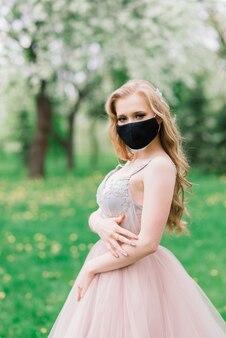 ウェディングドレスと咲くリンゴの木の近くの彼女の顔に黒い医療マスクの美しい若い花嫁。 covid19防止。