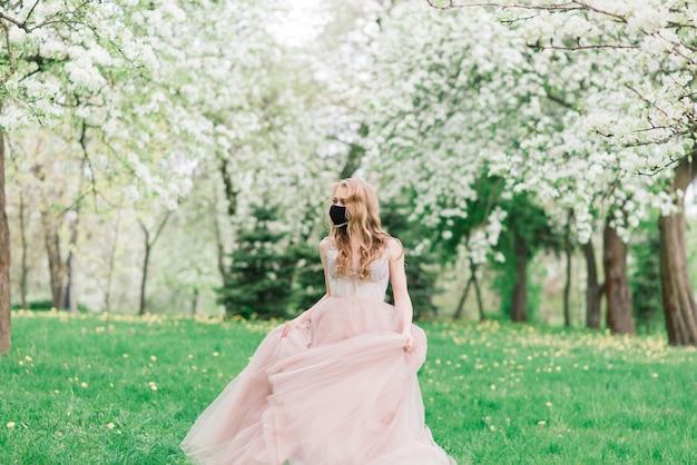 Красивая молодая невеста в свадебном платье и черной медицинской маске на лице возле цветущих яблонь. защита от covid-19.