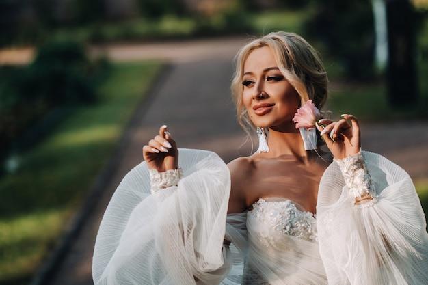 豪華な白いウェディングドレスの美しい若い花嫁。夏のフィールドでかわいい花嫁の肖像画。幸せな結婚式の日。メイクと髪型の美しい花嫁。