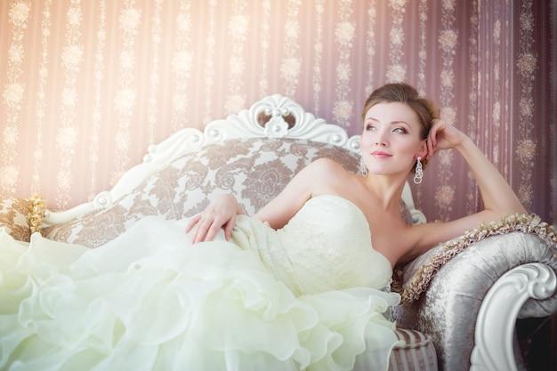 Красивая молодая невеста, лежа на роскошном софе.