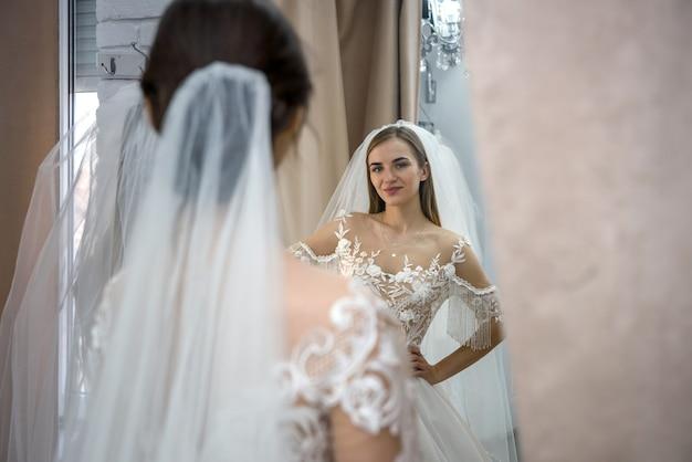 サロンでウェディングドレスでポーズをとる美しい若い花嫁
