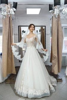 Красивая молодая невеста позирует в свадебном платье в салоне