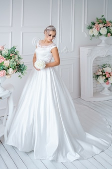 Beautiful young bride in a white dress and a bouquet of flowers in the studio