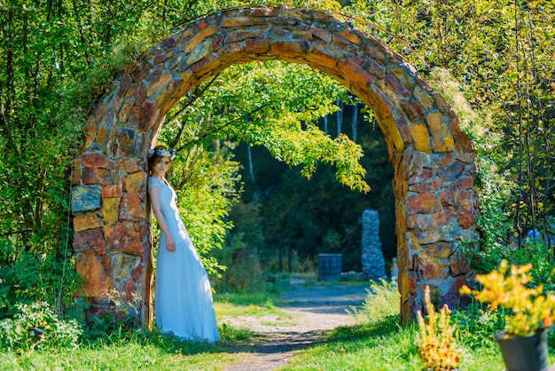 Beautiful and young bride in white dress and circlet of flowers posing in stone arch