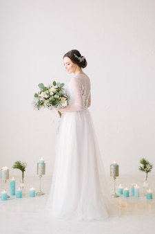 Beautiful young bride in a white dress with a bouquet of flowers posing in a hall with white walls and decorated floor with flowers and candles