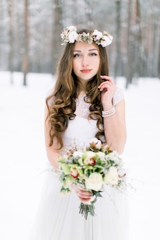Beautiful young bride in the winter snowy forest