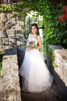 Красивая молодая невеста с букетом свадебных цветов. праздничное платье