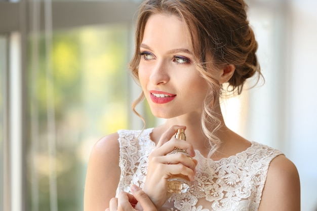 Beautiful young bride with bottle of perfume indoors