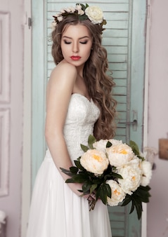 Beautiful young bride with crown flowers and romantic decoration pink and green. wooden boxes bottles and different wedding decoration