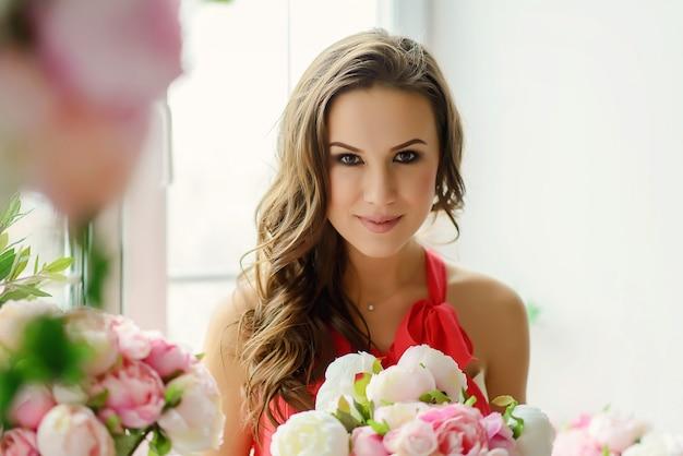 Красивая молодая кареглазая женщина с букетом цветов пионов в руках возле окна.