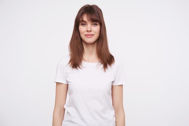 白い壁にポーズをとっている間、基本的な白いtシャツを着て、魅力的な笑顔で前向きに見える美しい若い茶色の髪の女性