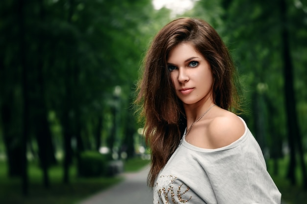 Beautiful young brown-haired girl in the park on a warm summer day