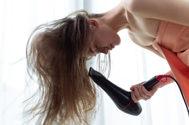 Beautiful young brown haired person in bath towel is using a hair dryer for drying her long hair after shower in room. hair care.