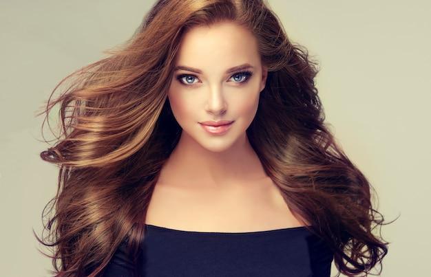 ボリュームのある、飛んでいる髪の美しい若い茶色の髪の女性。長くて密度の高いストレートな髪型と鮮やかなメイクの美しいモデル。理髪アート、ヘアケア、美容製品。