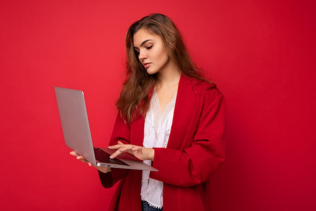 Beautiful young brunet woman holding netbook computer typing on keyboard