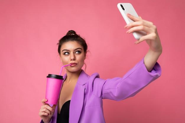 Красивая молодая брюнетка женщина в модном фиолетовом костюме на розовом