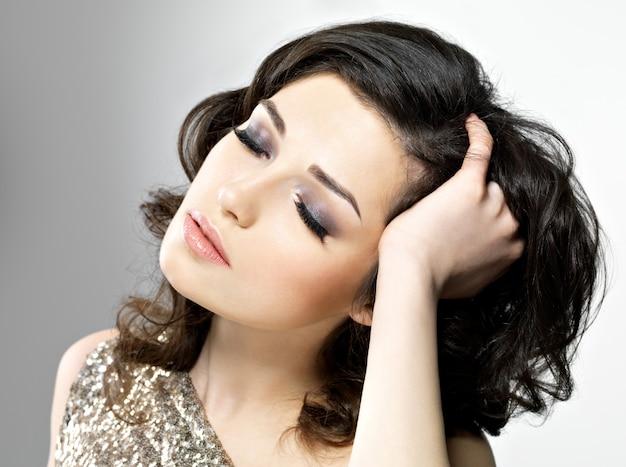 Красивая молодая брюнетка женщина трогает ее каштановые вьющиеся волосы