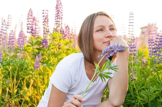 피는 야생 꽃 녹색 배경으로 여름 필드에 쉬고 아름 다운 젊은 brunete 여자