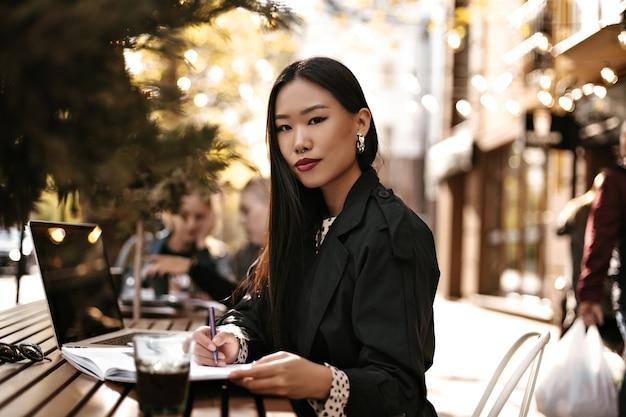 검은 트렌치 코트를 입은 아름다운 젊은 브루네트 아시아 여성이 카메라를 쳐다보고, 밖에 있는 나무 책상에 앉아 노트북에 메모를 합니다.