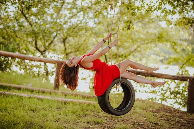 川の近くの森でタイヤのブランコに乗って赤い夏のドレスを着た美しい若いブルネット裸足の女性。スペースをコピーします。