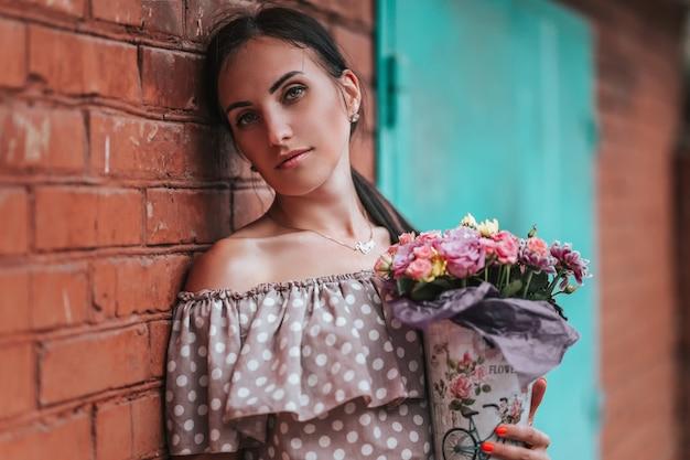 Beautiful young brunette in begie dot dress posing outdoor near red brick wall