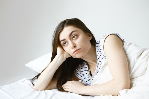 Bella giovane donna europea bruna in pigiama a righe sentirsi sola e annoiata a morte mentre giaceva a letto, guardando di traverso con espressione facciale premurosa