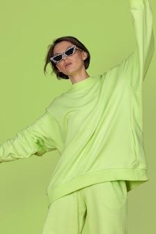 緑の背景に緑のカジュアルな服装でポーズをとって美しい若いブルネットのファッショニスタ