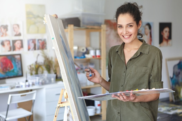 Beautiful young brunette female painter dressed casually while working in her workshop, standing near easel, creating picture with colorful watercolors