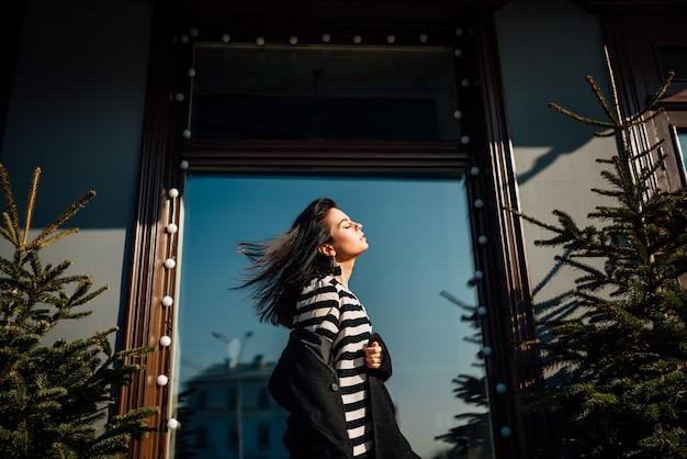 Красивая молодая брюнетка девушка в черном пальто гуляет по улицам города