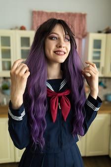 台所で自宅で日本の女子高生の制服を着た美しい若いブルネットの女の子