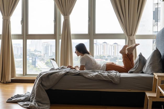 A beautiful young brunette girl is working on the laptop while lying on a bed by a panoramic window with a beautiful view from a high floor. stylish modern interior. a cozy workplace